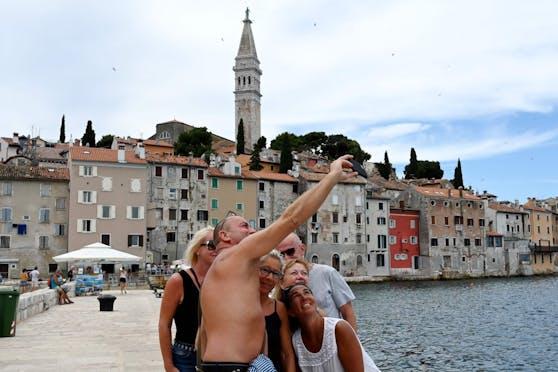 Touristen posieren vor der Stadtansicht von Rovinj (Kroatien) für ein Selfie
