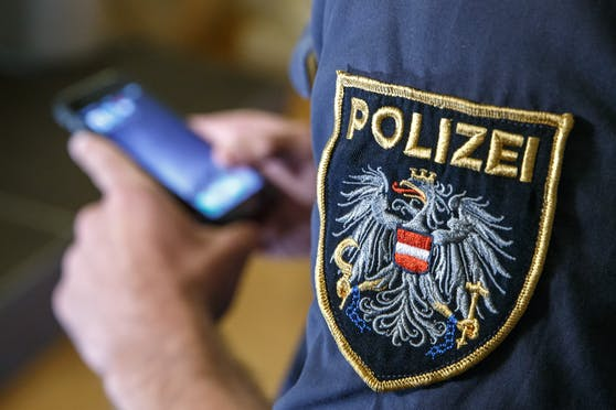 Ein Polizist hantiert an seinem Dienstsmartphone. (Symbolbild)