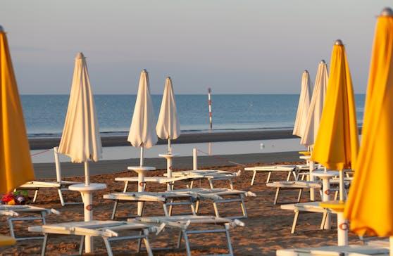 Leere Liegen und zugeklappte Schirme am Strand von Lignano. Archivbild