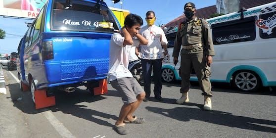 Leibesübungen als Strafe für das Nicht-Tragen einer Schutzmaske in Indonesien. (15. Mai 2020)