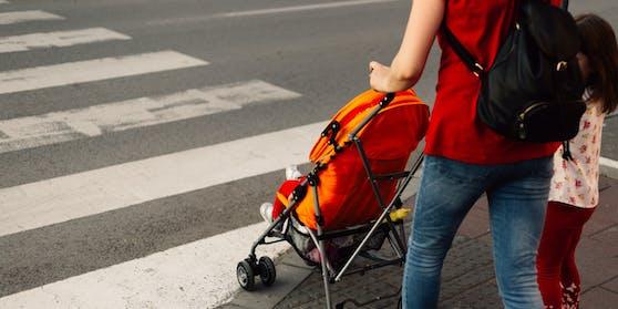 Eine Mutter mit ihren Kindern an einem Zebrastreifen. Symbolbild