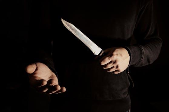 Der dunkel bekleidete Täter forderte mit einem Messer Geld. (Symbolbild).