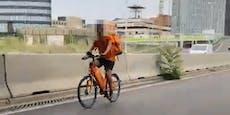Essenslieferant fährt mit Fahrrad auf der Autobahn