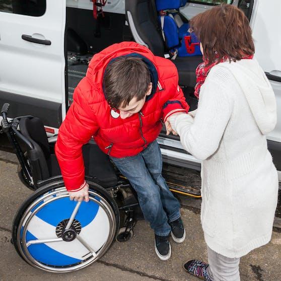 Eine Mutter hilft ihrem behinderten Sohn aus dem Schulbus. Symbolbild