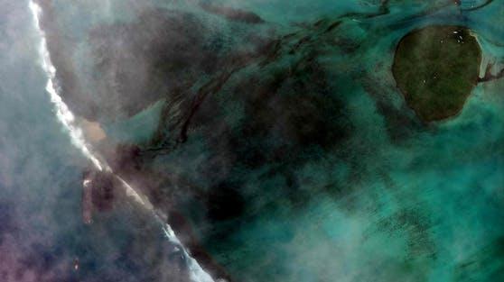 Aus der Wakashio, links unten im Bild, läuft tonnenweise Öl ins Meer. (7. August)