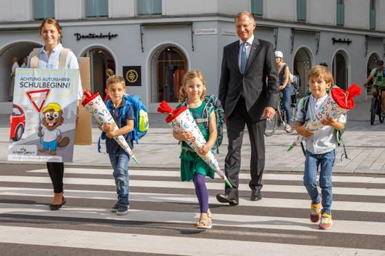 Landeshauptmann Thomas Stelzer bittet gemeinsam mit den Erstklässlern Anna, Anton und Matthäus um Vorsicht im Straßenverkehr.
