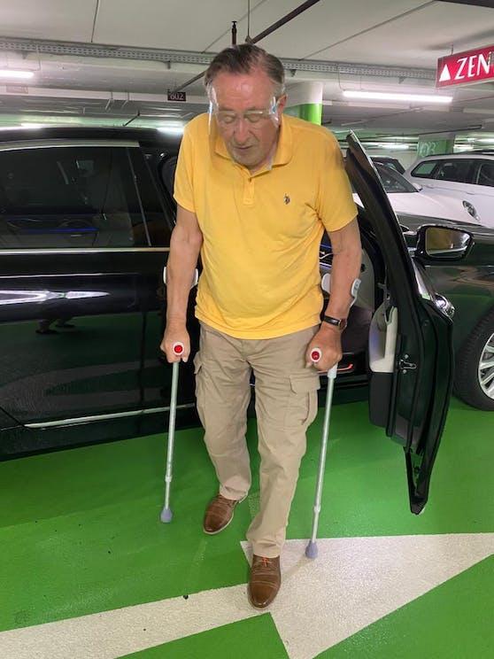 Richard Lugner mit Krücken in seiner Tiefgarage