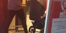 Mutter bindet Kind bei Einkauf mit Hand an Kinderwagen