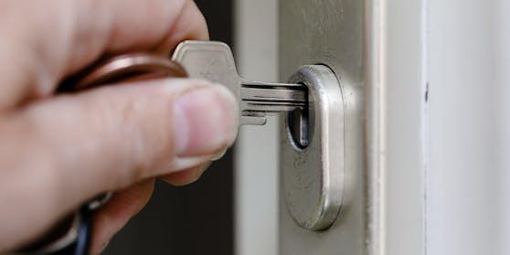 Ein Mann sperrt mit einem Schlüssel seine Wohnungstür. Symbolbild