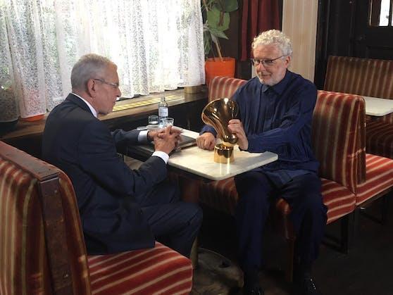"""Bundespräsident Dr.Alexander Van der Bellen (li.) überreicht André Heller die goldene """"Amadeus""""-Trophäe in einem von Wiens legendärsten Kaffeehäusern."""