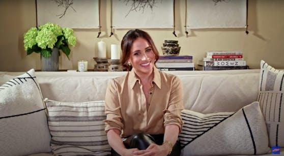 Meghan Markle gemütlich auf ihrem Sofa, umgeben von Kissen, Kerzen und Büchern in Santa Barbara.