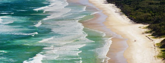 Surfer auf dem Weg ins Wasser am Tallow Beach in Australien.