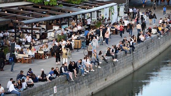 Junge Menschen stürmen bei Schönwetter die Promenaden am Wiener Donaukanal.