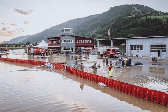 Zell am See: Einsatzkräfte der Feuerwehr pumpen nach den Sintflut-Unwettern Wasser am überfluteten Flugplatz ab