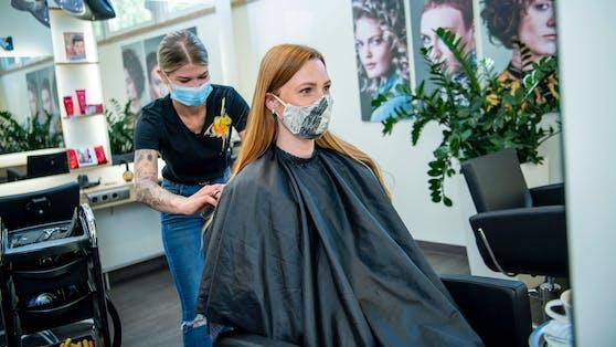 Eine Kundin lässt sich beim Friseur die Haare schneiden.