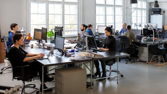 Mitarbeiter in einem Großraumbüro (Symbolbild)