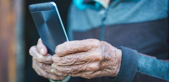 Symbolfoto eines alten Mannes mit Handy.