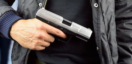 Ein Mann droht mit einer Pistole. Symbolbild