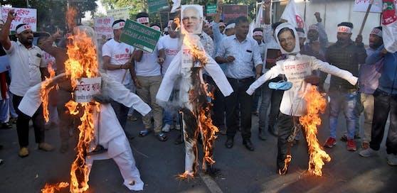 Aktivisten der All Assam Studentenverbindung verbrennen aus Protest Figuren, de Innenminister Amit Shah, die Premierminister Narendra Modi und den Ministerpräsidenten von Assam Sarbananda Sonowal zeigen.