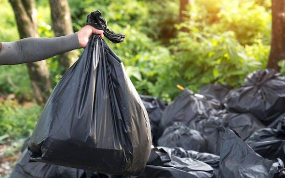 Ein Mann bringt Müllsäcke nach draußen. Symbolfoto