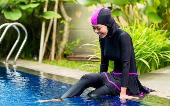 Eine Frau im Burkini am Rand eines Schwimmbeckens. Symbolfoto.