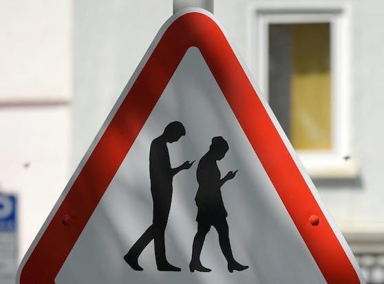 Smombies gefährden sich und andere im Straßenverkehr.