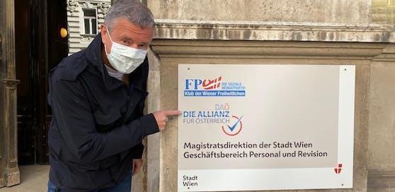 PR-Berater Gernot Rumpold, vorbildlich mit Maske, zeigt das neue Türschild der DAÖ-Zentrale. Die FPÖ residiert jetzt einen Stock höher.