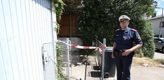 Ein Polizeibeamter bewacht den Eingang des Hauses in Linz-Dornach, wo der Doppelmord passierte.