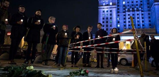 Menschen zünden vor dem Kulturpalast in Warschau Kerzen an. Hier steckte sich der Mann selbst in Brand.