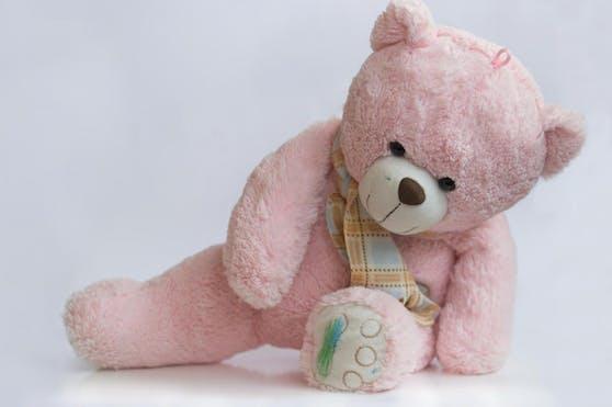 Rosa Teddybär mit farbigen Pfoten und Gesicht. Symbolfoto
