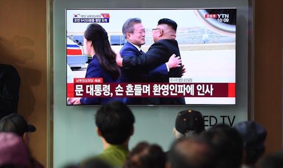 Südkoreas Präsident Moon Jae-in wird von Nordkoreas Staatschef Kim Jong-Un mit einer Umarmung herzlich begrüßt.