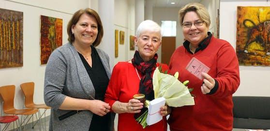Ernestine Kral freut sich über die Blumen und das Ehrengeschenk von Stadträtin Vera Edelmayr (l.) und Bürgermeisterin Karin Baier (r.).