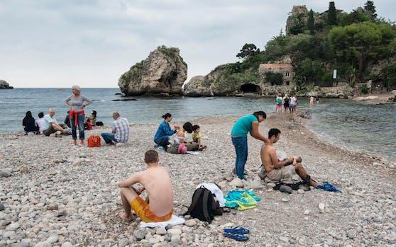 Eine Frau massiert Touristen am Strand von Taormina, Italien.