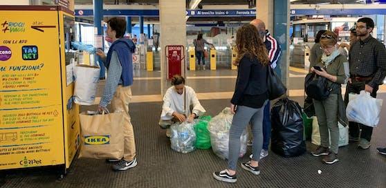 Menschen stehen Schlange, um Plastikflaschen gegen Tickets einzutauschen.