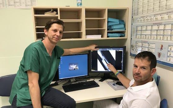Die beiden Chirurgen Stefan Froschauer (li) und Richard Schnelzer vor dem Röntgenbild des abgetrennten Armes des Pensionisten.