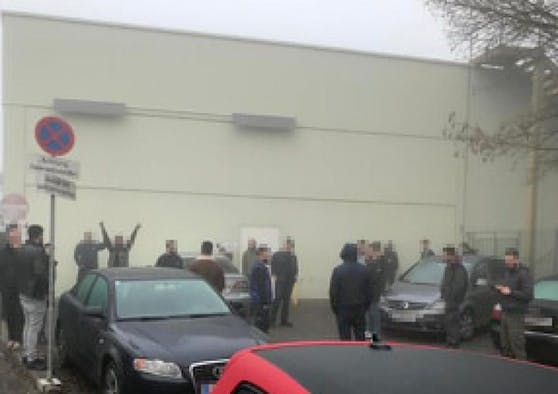 Die Arbeiter versammelten sich vor dem Firmengebäude.