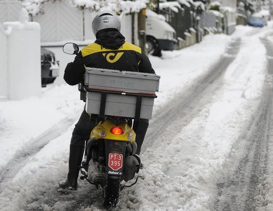 Ein Briefträger der Österreichischen Post AG mit dem Motorroller auf rutschiger Schneefahrbahn. Archivbild: 29. November 2010, Wien.