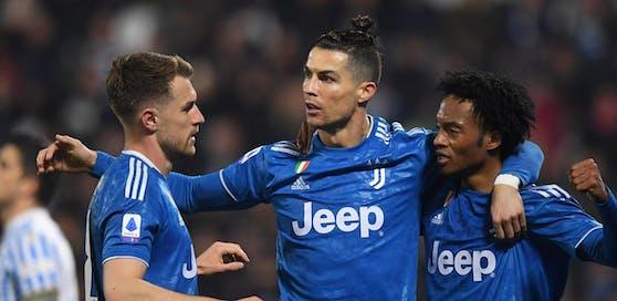 Cristiano Ronaldo mit seinen Juve-Kollegen Aaron Ramsey und Juan Cuadrado - in Zeiten, als Abstand halten noch nicht Pflicht war.