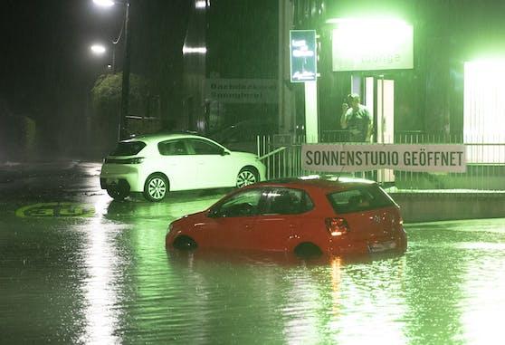 Ein Fahrzeug auf einer überfluteten Kreuzung nach schweren Unwettern am Freitag, 30. Juli 2021, in Graz.