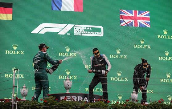 Sieger Esteban Ocon und Sebastian Vettel feiern mit der Champagner-Dusche, Lewis Hamilton kämpft sichtlich mit Kreislaufproblemen.