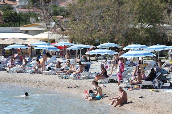 Badende an einem kroatischen Strand. Die Coronazahlen bei den Reiserückkehrern explodieren förmlich.