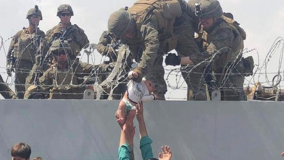 Verzweifelt reichte ein Vater sein Baby über einen Stacheldraht an US-Soldaten weiter.
