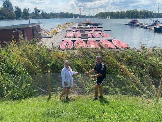 Marianne Kukla und FPÖ-Gemeinderat Toni Mahdalik vor dem neuen Zaun, der die Schwanenfamilie in Wien-Donaustadt von der Straße fernhalten soll.