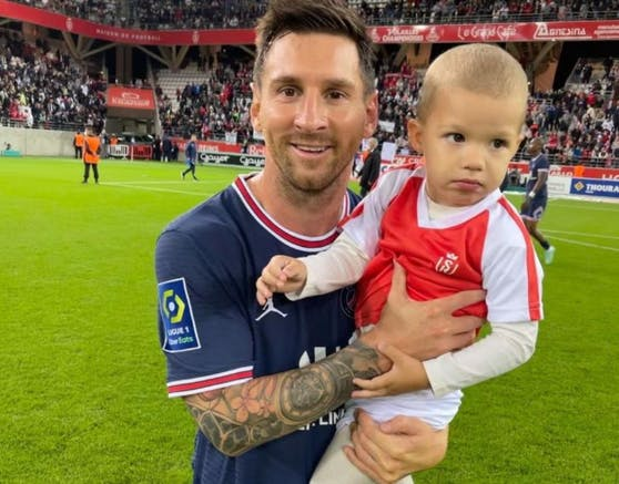 Lionel Messi posiert mit dem Kind von Reims-Goalie Predrag Rajkovic