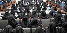 Verschleierte Frauen mit Taliban-Fähnchen im Uni-Saal