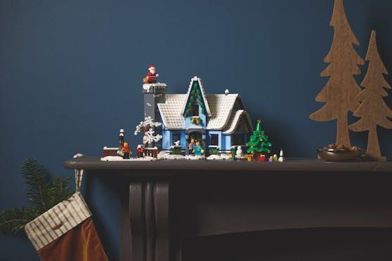 """Der Mittelpunkt des """"LEGO Besuch vom Weihnachtsmann""""-Sets ist ein mit Stechpalmenzweigen geschmücktes kleines Häuschen mit verschneitem Tor samt Briefkasten."""