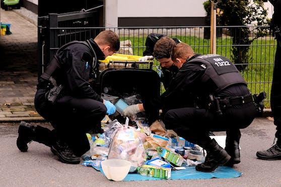 Die Polizei durchsucht den Müll in der Nähe des Tatorts.