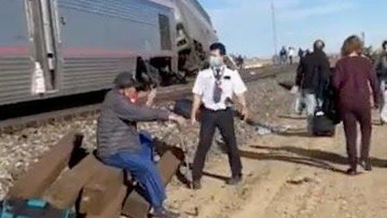 Mehrere Wagen entgleist: Die Leute warten neben dem Zug auf Hilfe. (25. September 2021)