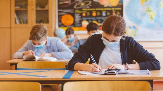 High school students at school, wearing N95 Face masks. Sitting in a classroom.