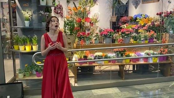 Sängerin Ksenia Skorokhodova bringt singend Blumen.